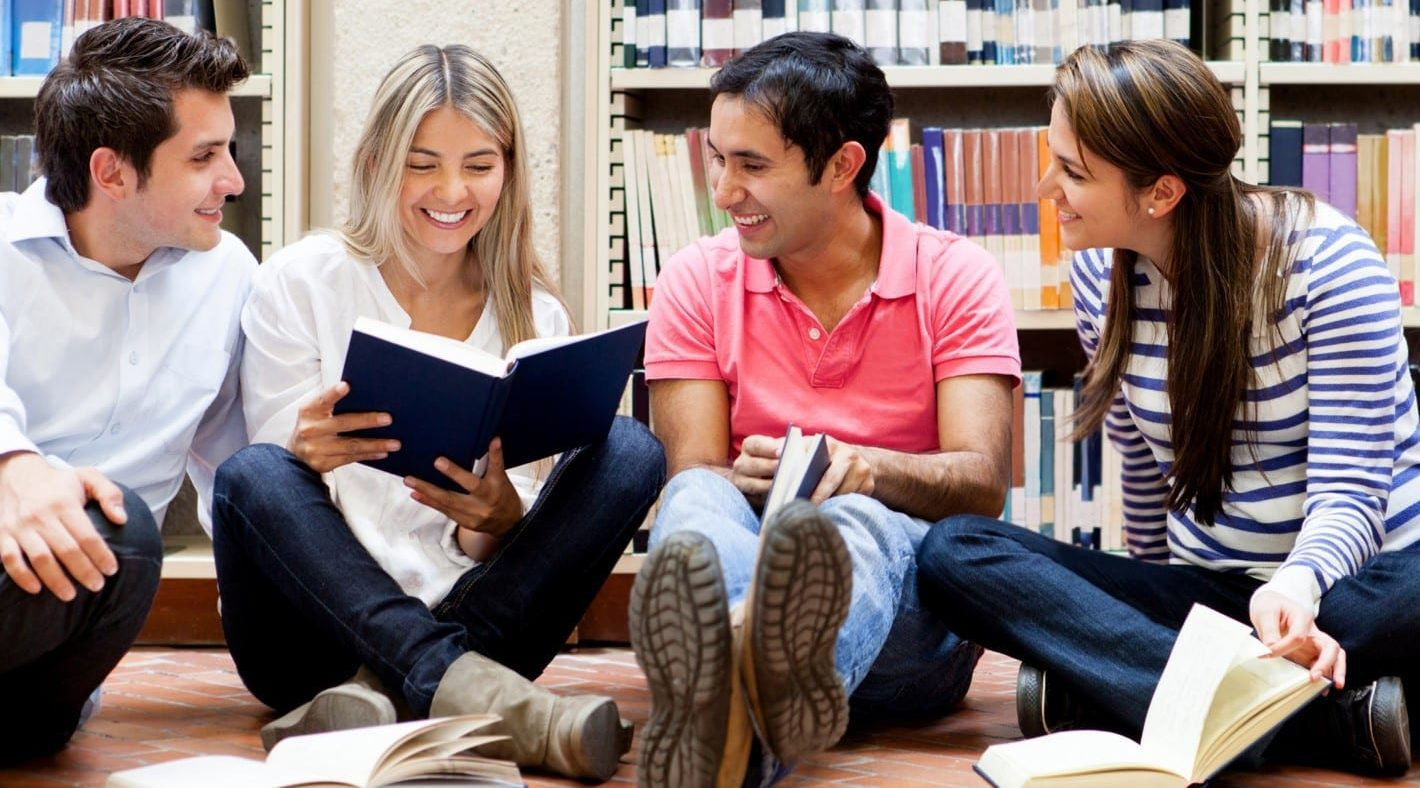 Group of students reading in a library